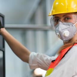 Operaia al lavoro con dispositivi di sicurezza